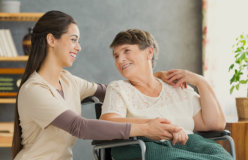 Portrait of senior woman in a wheelchair and a young caregiver