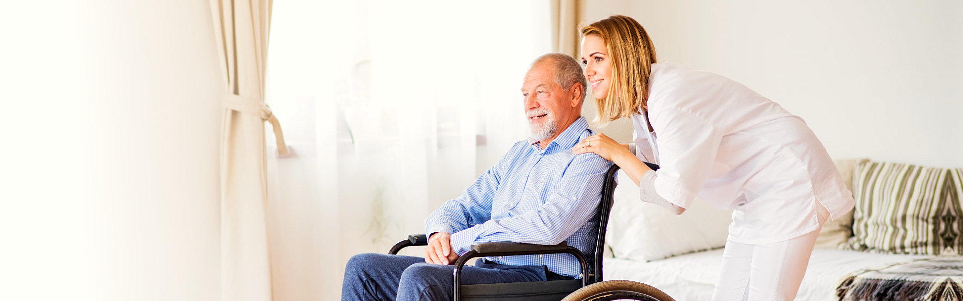 Portrait of senior man in a wheelchair and young caregiver
